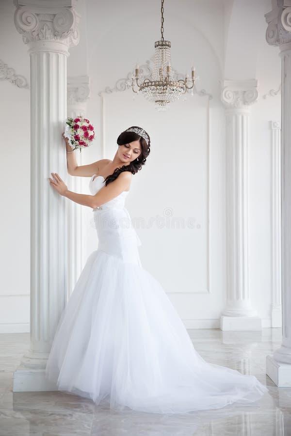 婚礼礼服的美丽的深色的新娘和在她的头,全长画象的一个冠 库存照片