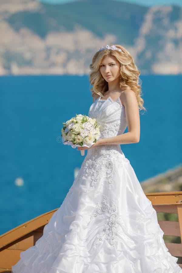 婚礼礼服的美丽的白肤金发的新娘与花o花束  免版税库存图片