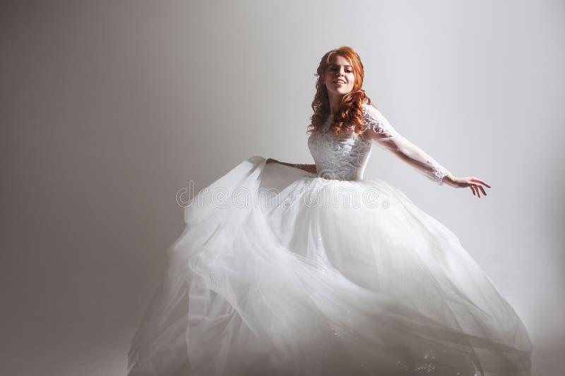 婚礼礼服的跳舞的少妇 轻的背景的迷人的新娘与阴影 免版税库存图片