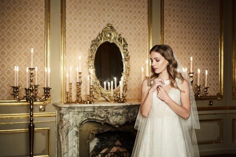 婚礼礼服的迷人的年轻新娘在巴洛克式的样式的内部摆在 浪漫纵向 免版税库存图片