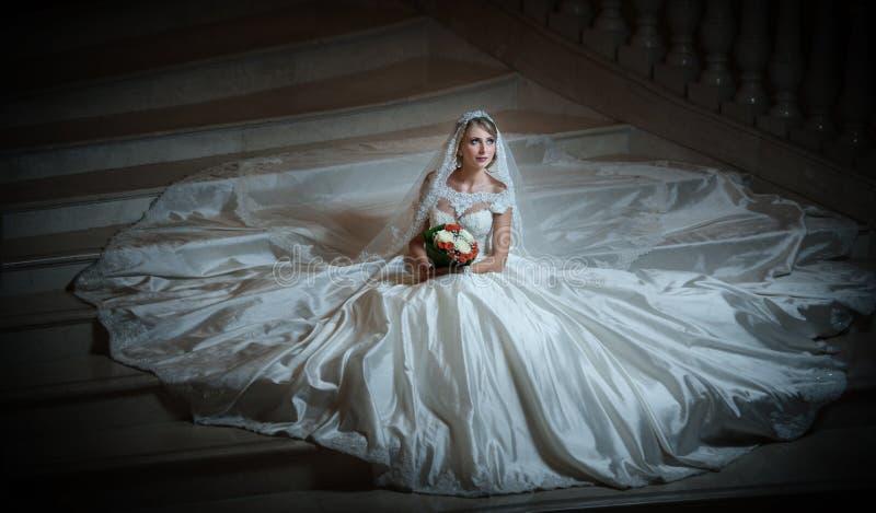 婚礼礼服的年轻美丽的豪华妇女坐台阶在半暗跨步 有巨大的婚礼礼服的新娘 免版税库存照片