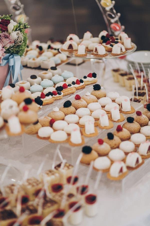 婚礼糖果棒 美味的奶油甜点,包括水果、芭娜柯塔、蛋糕和饼干,放在桌上,在2014年11月1日的婚礼前台举行 库存图片