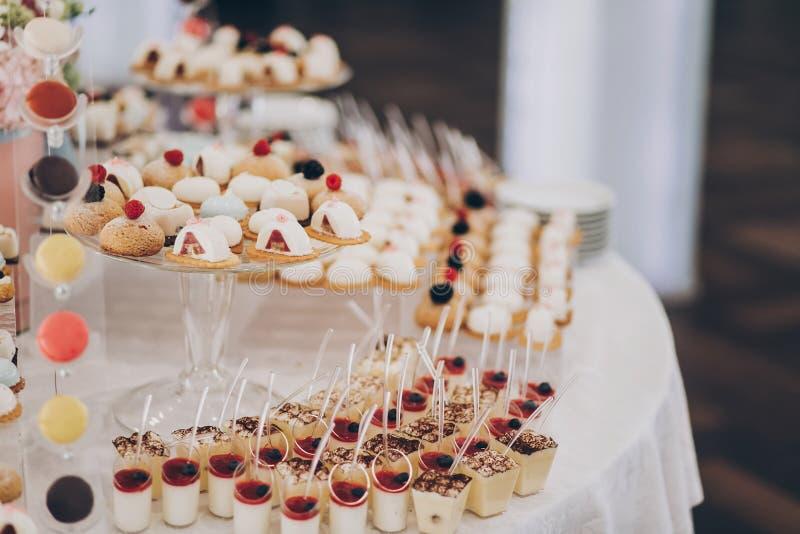 婚礼糖果棒 美味的奶油甜点,包括水果、芭娜柯塔、蛋糕和饼干,放在桌上,在2014年11月1日的婚礼前台举行 免版税图库摄影
