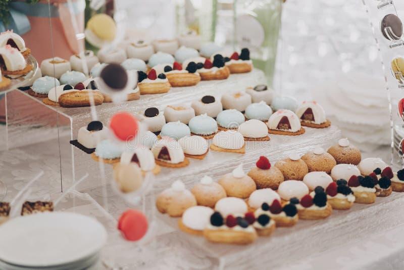 婚礼糖果棒 餐厅的婚宴上,在桌上提供美味的奶油甜点,包括水果、麦卡龙、蛋糕和饼干 库存照片