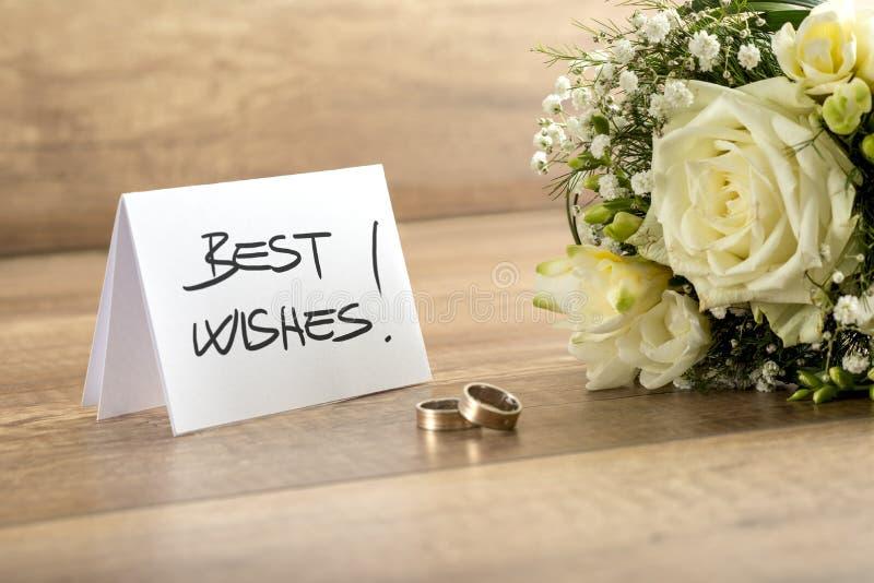 婚礼花、圆环和卡片在木表上 库存图片