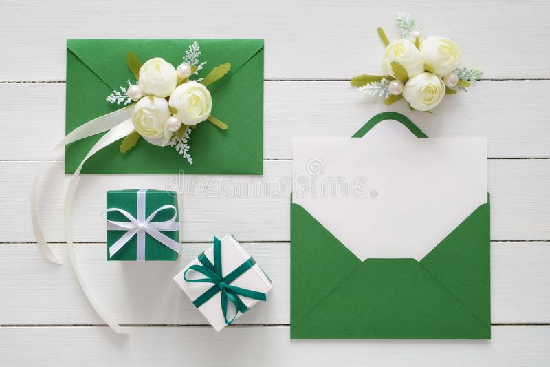 婚礼邀请卡片或情人节etters在用白色玫瑰装饰的绿色信封开花和两个礼物盒 平的la 库存图片