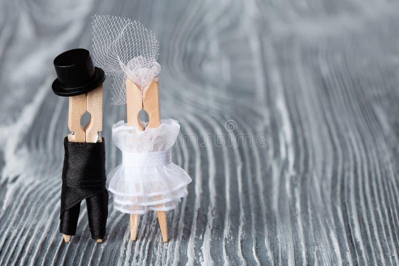 婚礼邀请卡片模板 晒衣夹在灰色木背景的黑衣服和新娘白色礼服修饰 库存图片