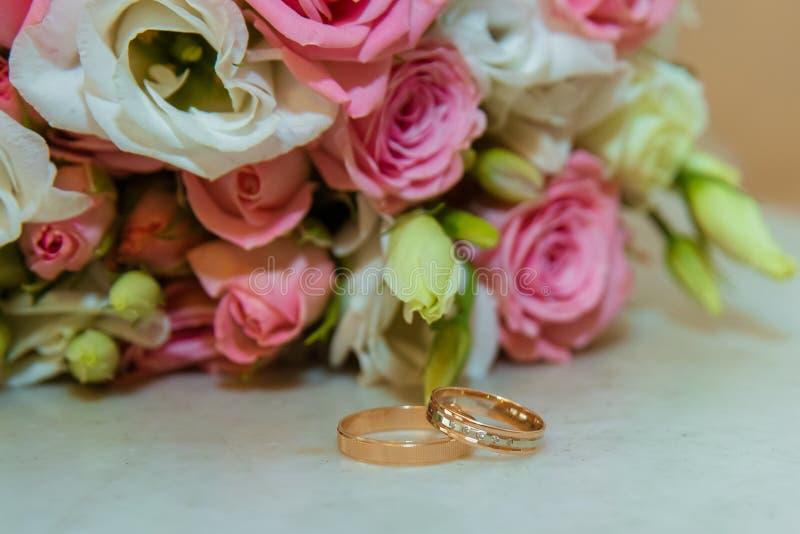 婚礼金戒指 浪漫订婚两钻戒在桃红色玫瑰和白花附近新娘的花束  免版税库存照片