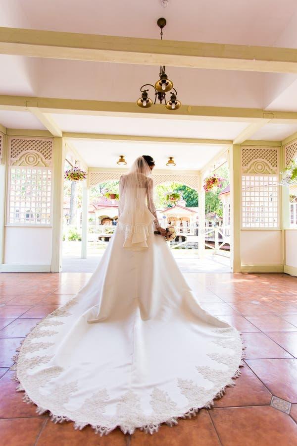 婚礼,拿着美丽的花束的新娘后边 库存图片