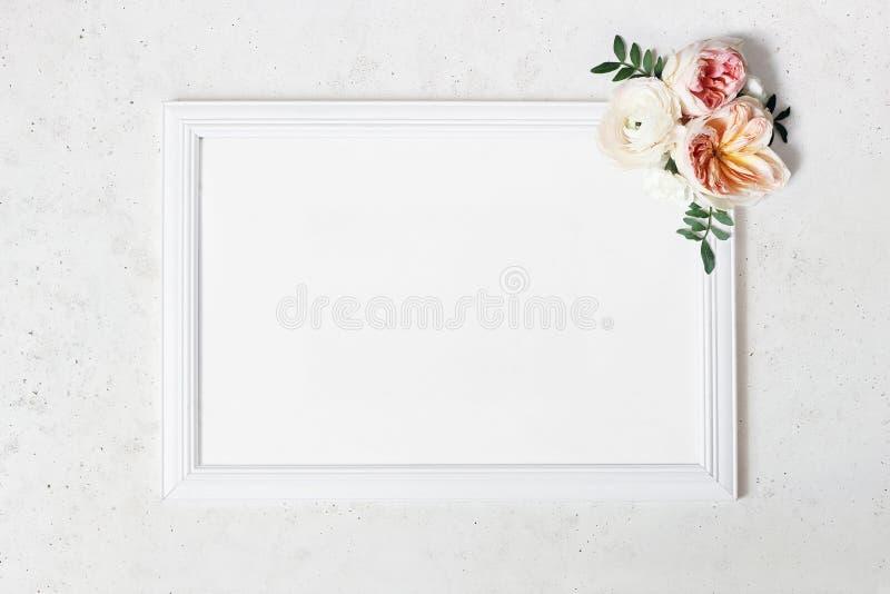 婚礼,生日标志板大模型场面 空白白色木制框架 装饰花卉角落 绿色叶子,桃红色 库存照片