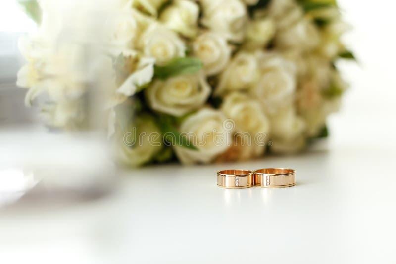 婚礼结构的在白玫瑰被弄脏的背景花束的婚戒  免版税库存图片
