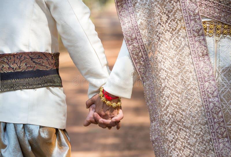 婚礼[特点泰国]礼服奔跑的亚裔夫人与她的丈夫 免版税库存图片
