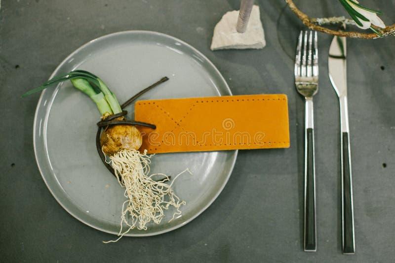 婚礼水仙碗筷、葱与皮革名片的,银色叉子和银刀子 库存照片