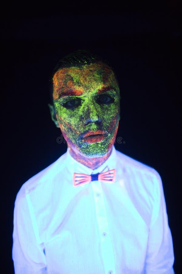 婚礼photosession的概念在霓虹照明设备正在流行的样式新郎年轻人的在黑暗摆在发光在白色 免版税库存照片