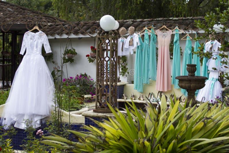婚纱、绿色女傧相和垂悬的小的页准备好仪式 免版税图库摄影