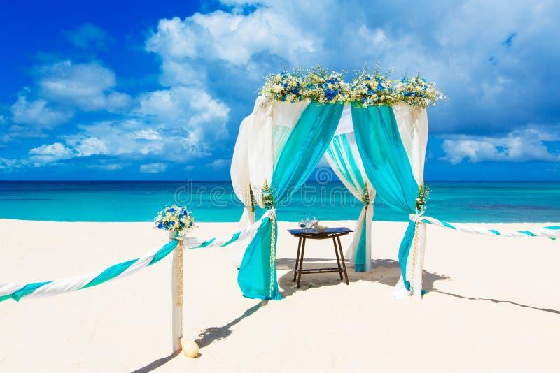 婚姻在海滩 用在tr的花装饰的婚礼曲拱 库存图片