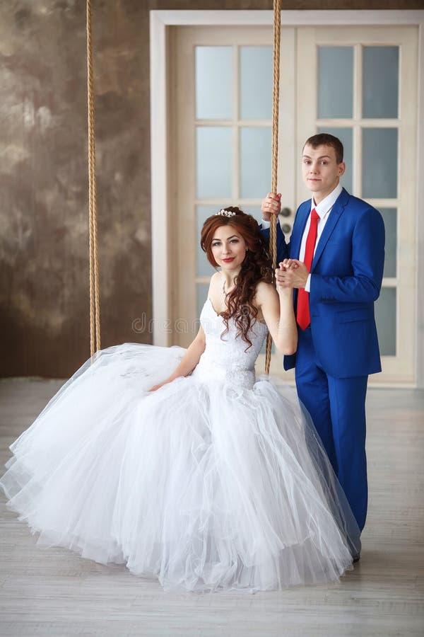 婚姻 愉快的新娘坐摇摆和新郎 婚姻概念 免版税库存图片