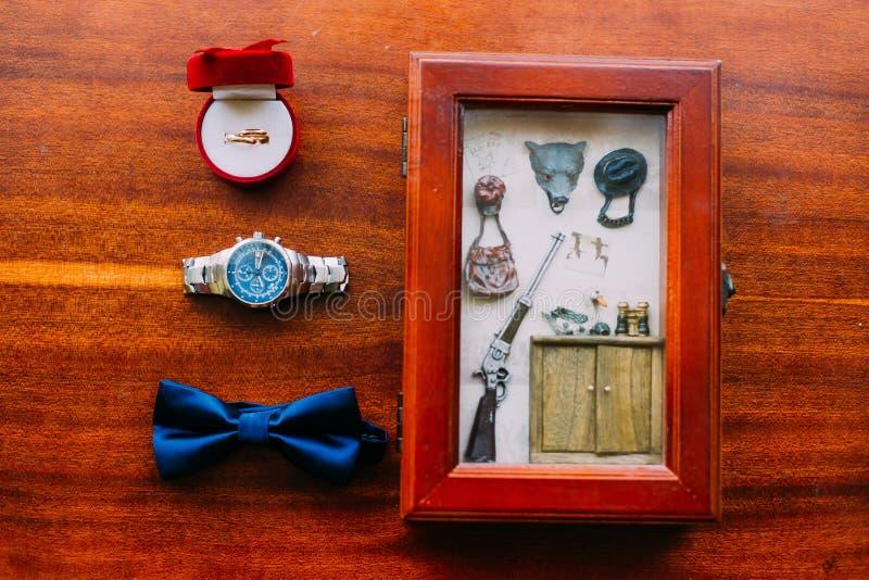 婚姻的套人` s时髦的手表和弓领带在棕色木背景与金黄圆环和明信片在土气 免版税库存照片