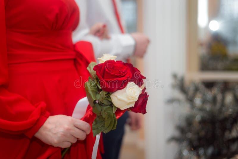 婚姻:新娘和新郎在新娘的手上结婚,红色和白玫瑰花束  库存照片