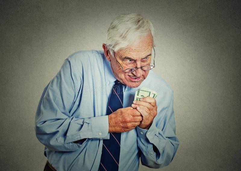 贪婪的执行委员, CEO,控制拿着美元钞票的成熟人 库存照片