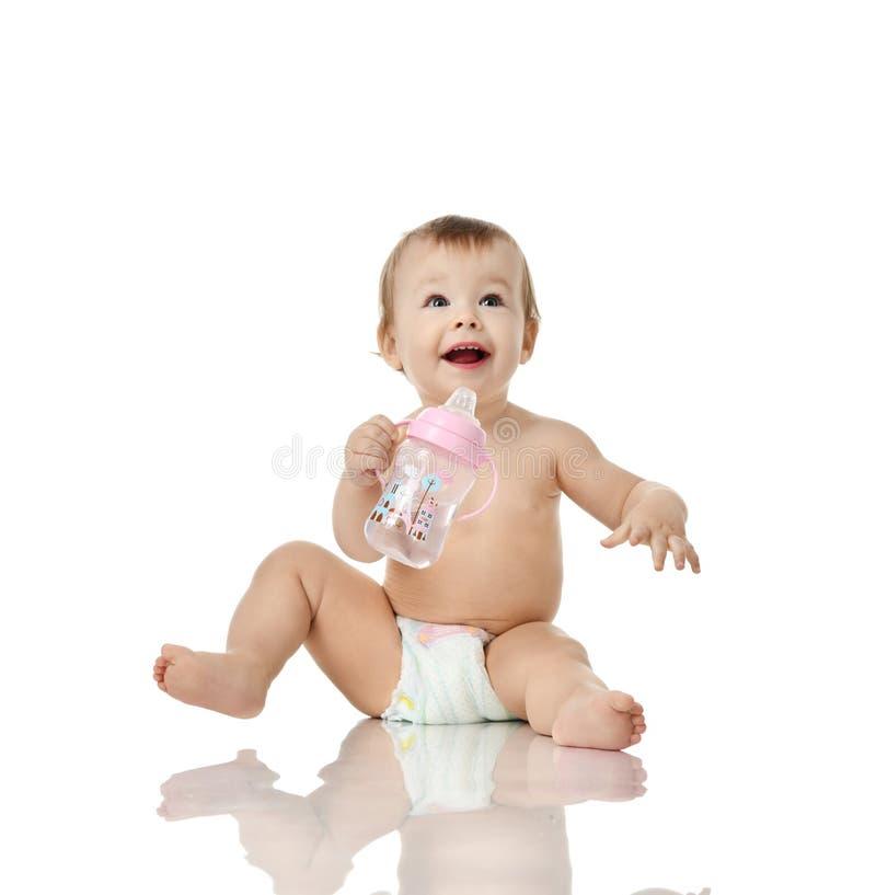 婴儿儿童女婴小孩举行饮用的哺乳瓶愉快微笑的查寻 免版税库存照片