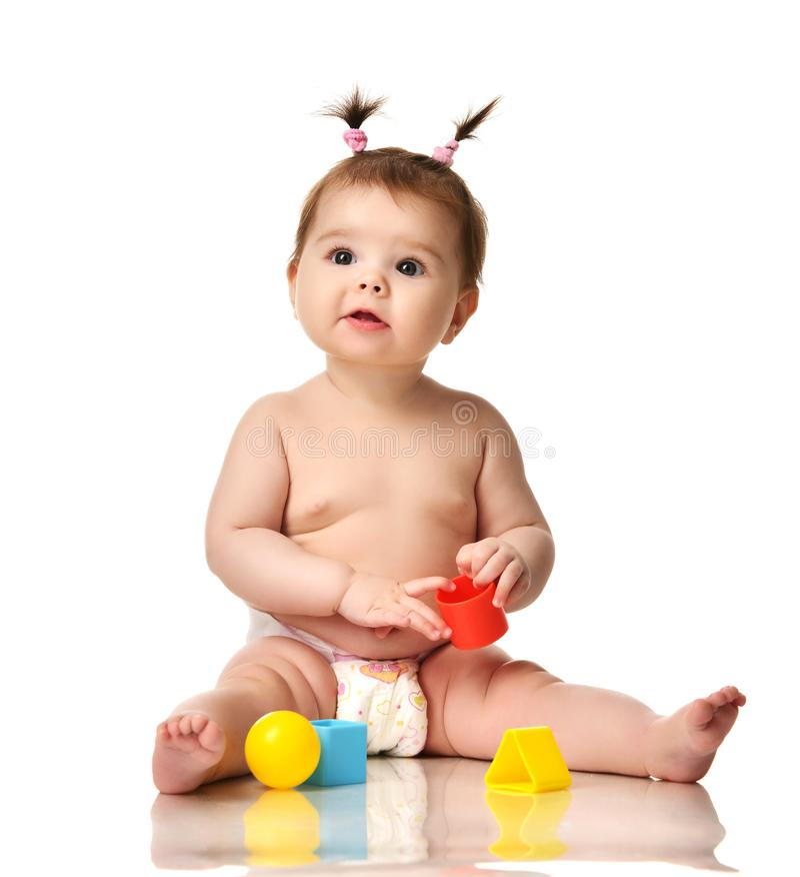 婴儿儿童小小孩坐赤裸在有黄色蓝色和红色教育玩具使用的尿布被隔绝的 免版税库存照片