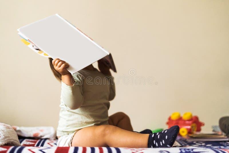 婴儿坐在沙发上,头顶藏在书后面 复制空间 免版税库存图片