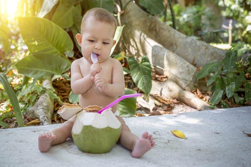 婴儿婴孩热带假期 吃并且喝绿色年轻椰子 坐地面并且拿着匙子 背景的密林 免版税库存照片