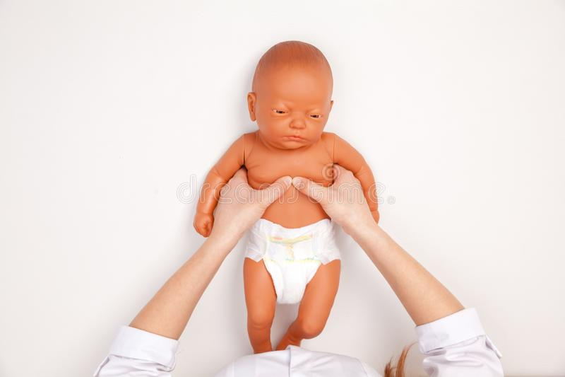 婴儿急救训练-显示手工胸口压缩的医生 库存照片