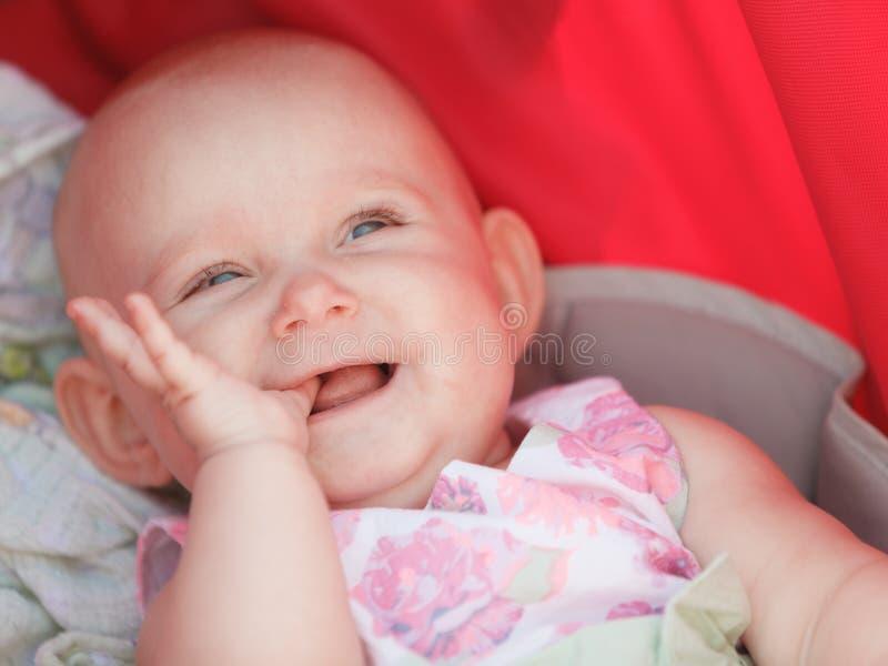 婴儿推车的小愉快的婴孩 免版税库存图片