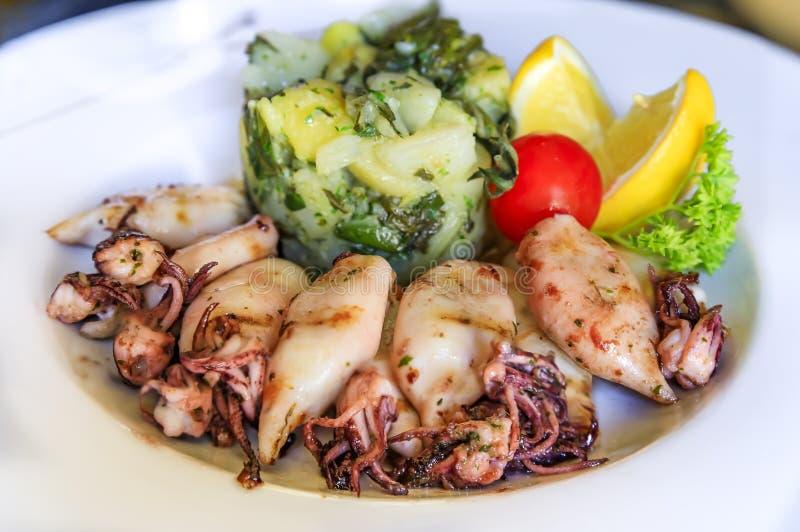 婴孩乌贼和blitva,土豆泥用唐莴苣,供食用莴苣、柠檬和蕃茄在一家餐馆在黑山 库存图片