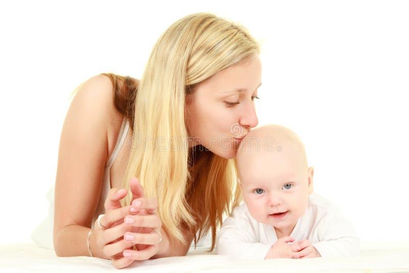 婴孩亲吻的母亲年轻人 免版税库存照片