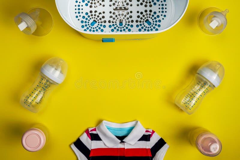 婴孩关心辅助部件和婴孩衣物在黄色背景 库存照片