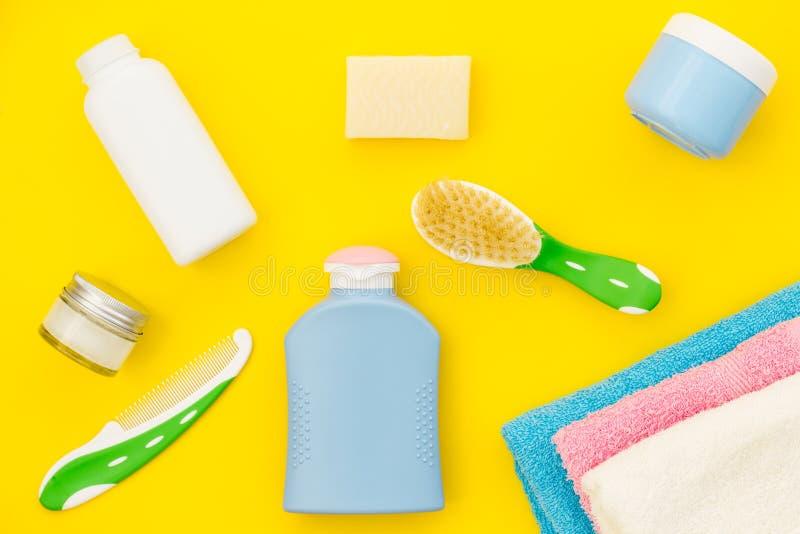婴孩关心 巴恩化妆用品和辅助部件孩子的 香波,胶凝体,奶油,牙在黄色背景上面掠过,梳 库存照片