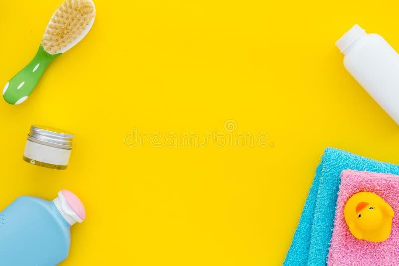 婴孩关心 巴恩化妆用品和辅助部件孩子的 香波,胶凝体,奶油,梳子,在黄色背景的黄色橡胶鸭子 免版税库存图片