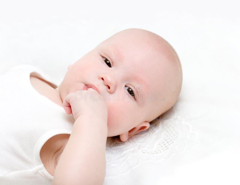 婴孩凹道您的拳头到嘴里 免版税图库摄影