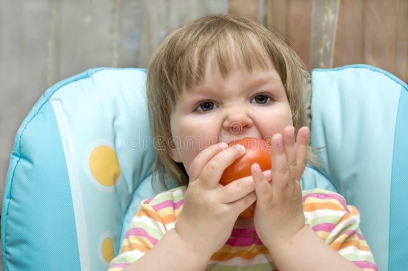 婴孩叮咬蕃茄 库存照片