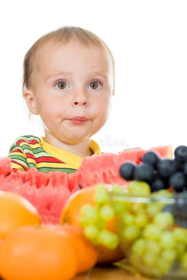 婴孩吃在一个空白背景的果子 免版税库存照片