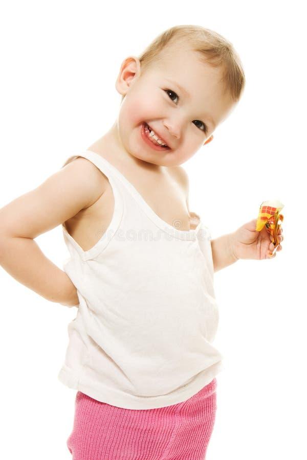 婴孩吃在一个空白背景的糖果 免版税库存照片