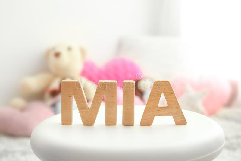 婴孩名字MIA组成由在凳子的木信件 免版税图库摄影