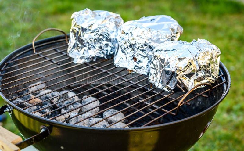 婴孩后面取笑在BBQ烤肉水壶格栅的冠烘烤 免版税库存图片