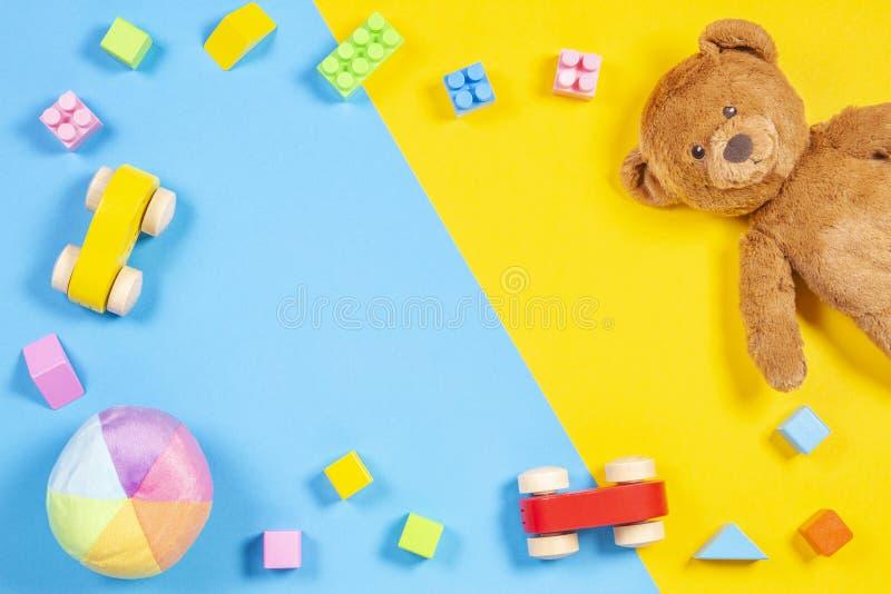婴孩哄骗与玩具熊,木玩具汽车,在蓝色和黄色背景的五颜六色的砖的玩具框架 顶视图 免版税库存图片