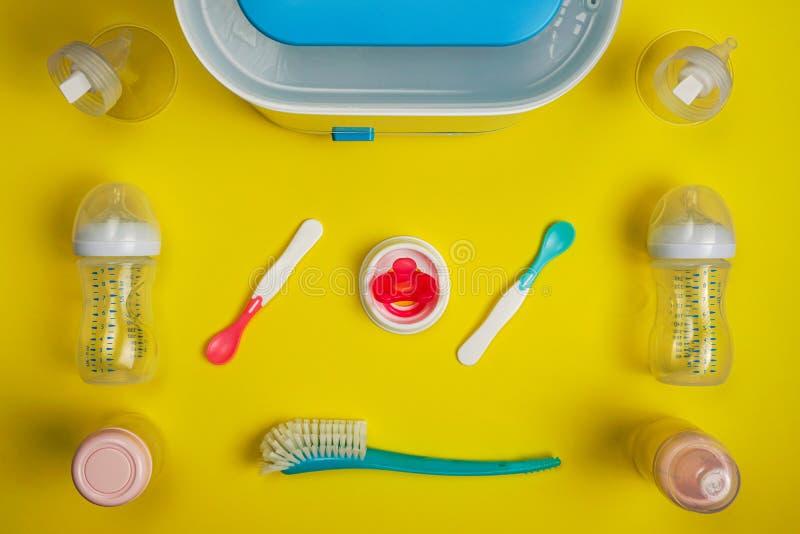 婴孩哺养的匙子、瓶消毒器、抽乳器耳轮缘和安慰者 图库摄影