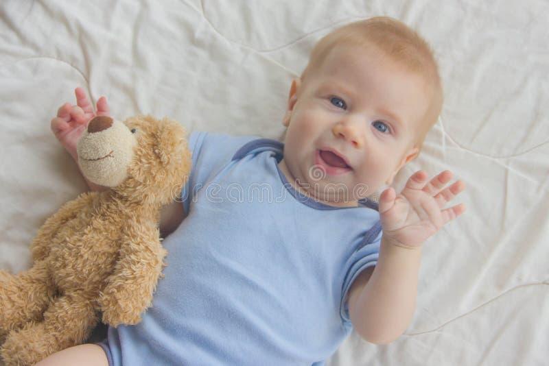 婴孩在与玩具熊的地板上说谎 儿童挥动他 免版税图库摄影