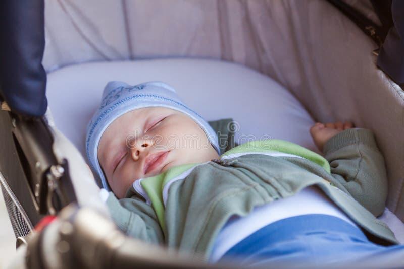 婴孩在摇篮车睡觉,当家庭步行时 库存照片