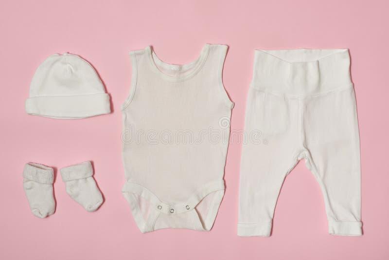 婴孩在桃红色背景的时尚概念 盖帽、紧身衣裤、裤子和袜子 免版税库存照片