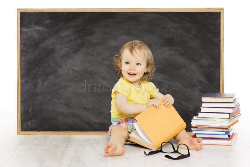 婴孩在黑板,孩子学校黑色板附近读了书 免版税库存照片