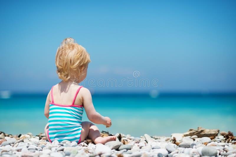 婴孩坐海滩。 背面图 图库摄影