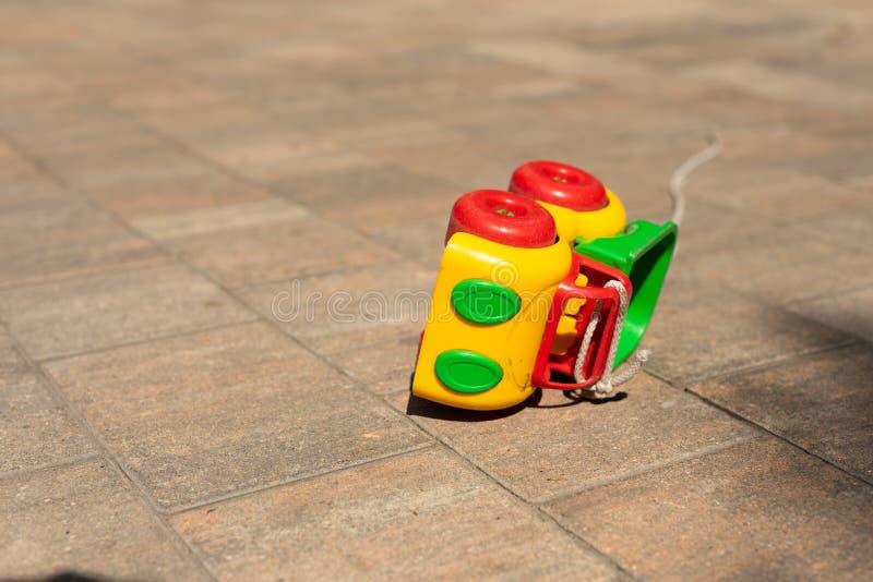婴孩孩子戏弄背景:玩具色的汽车在铺路石敲了  免版税库存照片