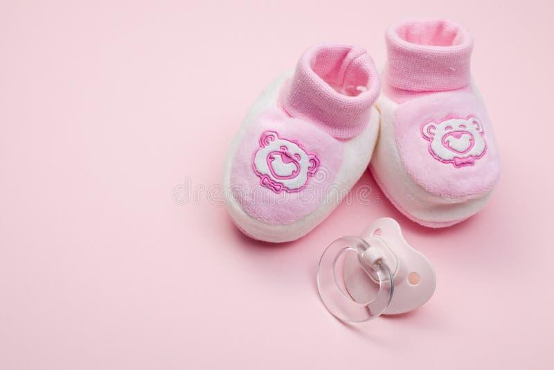 婴孩安慰者粉红色鞋子 免版税库存照片